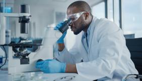 Químico olhando alguma coisa em microscópio