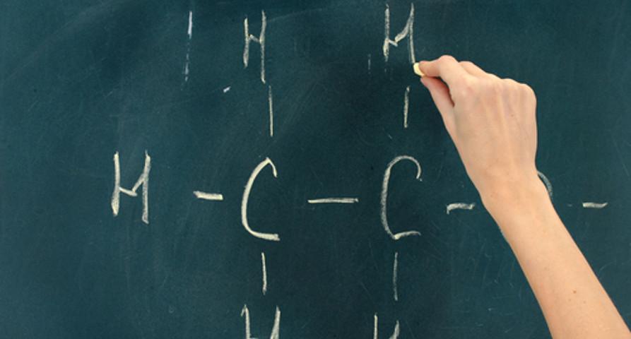 Aluno aprendendo a escrever a estrutura de uma cadeia carbônica no quadro-negro
