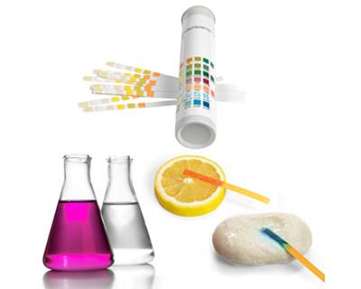 Exemplos de indicadores ácido-base usados em laboratório de química (indicador universal, fenolftaleína e papel de tornassol)