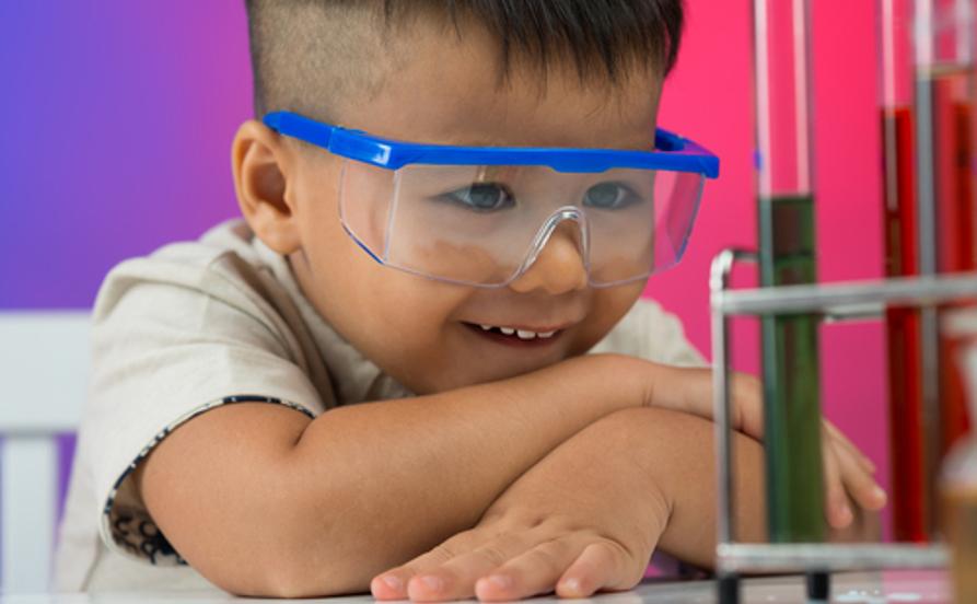Garoto observando uma curiosidade de Química em experimento