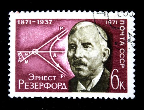 Um selo impresso na URSS mostra Ernest Rutherford, por volta de 1972, e, ao fundo, uma ilustração do seu experimento *